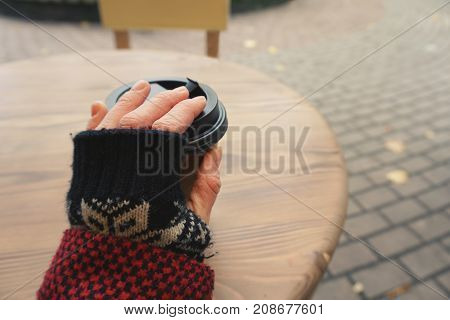 The hand of an elderly woman in warm clothes holds a plastic cup with coffee. Wooden table in the park on a blurry background.