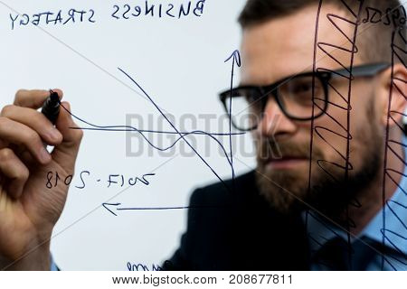 Businessman draws various growth charts calculating prospects for success in a modern glass office