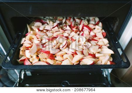 The process of drying apples in the oven. Pieces of apples on a metal black baking sheet.