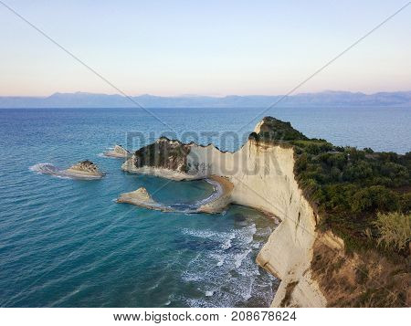 Aerial photo of Cape Drastis at Corfu island in Greece at sunset. Picturesque coast of Corfu island. Beautiful sea landscape