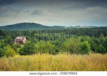 Cloudy rural landscape. Country house among the green hills.
