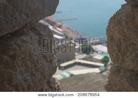 Sudak Crimea Russia June 29 2017: View from the loophole of the fortress on town named Sudak with coast pier and sea