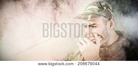 Soldier covering his mouth against black