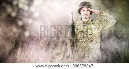 Portrait of soldier holding rifle and saluting against dark background