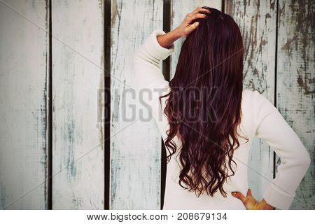 Full length rear view of brunette with hand in hair against wood panelling in pattern