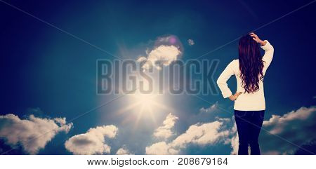 Full length rear view of brunette with hand in hair against sky