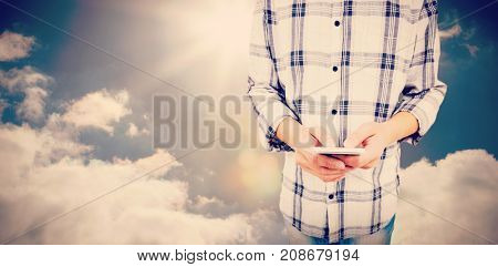 Mid section of man using smart phone  against sky