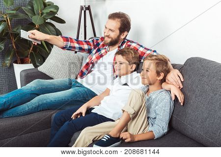 happy father with remote controller and cute little sons watching tv together at home