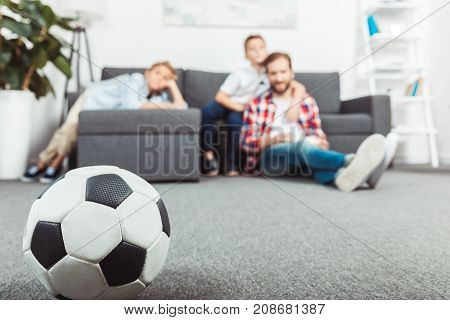 close-up view of soccer ball and father with sons sitting behind