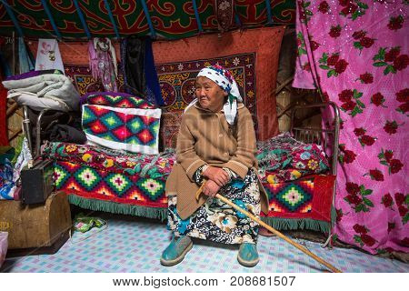 BAYAN-OLGII, MONGOLIA - SEP 28, 2017: Kazakh old woman from family of hunters with hunting birds (golden eagles) inside the mongolian Yurt. In Bayan-Olgii Province is populated with Kazakhs to 88,7 %
