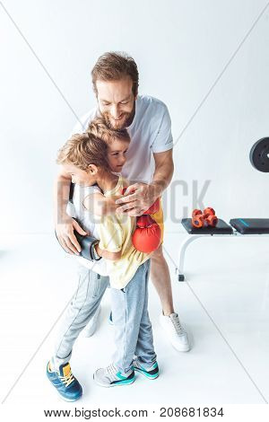 Father Hugging Sons In Boxing Gloves