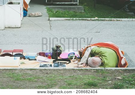 Poor homeless street vendor sleeps on the ground covered with blanket. Novi Sad, Serbia. October - 08. 2017. Editorial image.