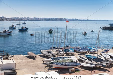 Bay Of Cascais. Small Sailing Boats Lay On The Pier
