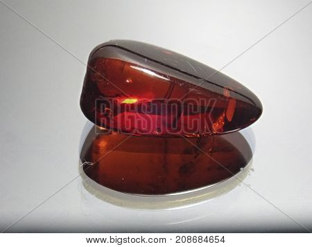 translucent red amber with internal impregnations on a gray background