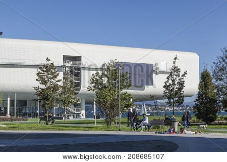 SANTANDER SPAIN - OCTOBER 7 2017: Tourists and local citizens relax on the promenade near the Centro Botin. The building was designed by Italian architect Renzo Piano.