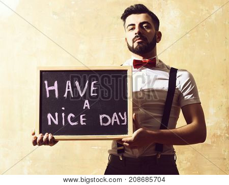 bearded man long beard brutal caucasian hipster with moustache in white shirt and suspenders bow-tie holding board and inscription have a nice day serious face on studio wall background