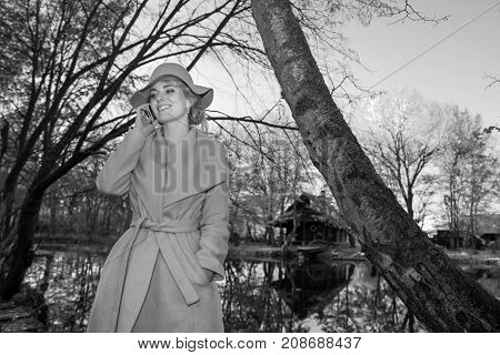 beautiful woman in a coat hat and a white dress for a walk in an autumn park or forest. retro wedding style 50-ies. monochrome black and white photo