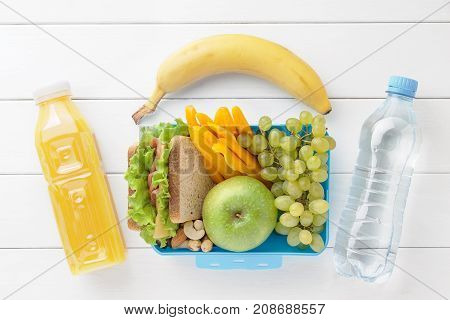 Lunch box with healthy food ready to eat. Plastic container with sandwich apple grape sweet pepper banana and bottles of water and juice on white wooden table. Concept of lunch time top view.