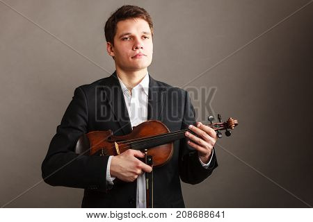 Music passion hobby concept. Man man dressed elegantly holding wooden violin. Studio shot on dark background