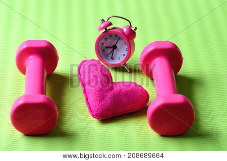 Morning Workout Concept. Dumbbells In Pink Color Near Alarm Clock