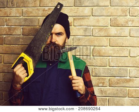 Bearded Worker Man Holding Saw And Hammer With Serious Face