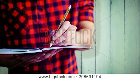 Hipster taking notes on notebooks against wooden planks