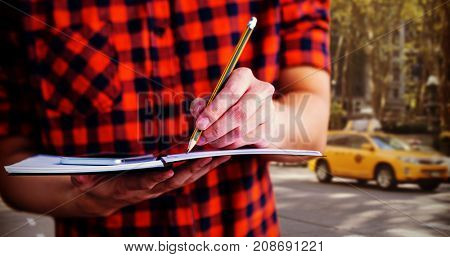 Hipster taking notes on notebooks against view of a city