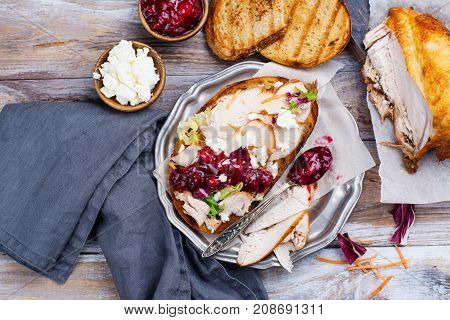Homemade leftover thanksgiving day sandwich with turkey, cranberry sauce, feta cheese and vegetables