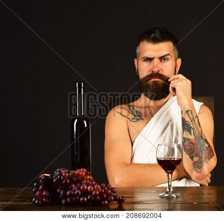 Man with beard near glass of alcohol on brown background. God Bacchus with strict face wearing white cloth sits by wine bottle and grapes. Viticulture and grape harvest concept. Sommelier tasting wine