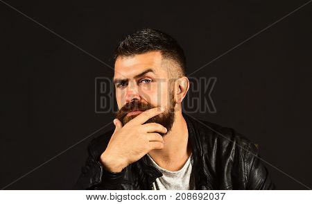 Man With Beard Wears Black Jacket. Guy With Suspicious Face