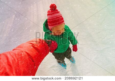 parent teaching child to skate in winter nature