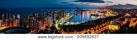 Malaga Spain. Aerial view of City Hall port and Bullring arena with illuminated buildings and Mediterranean sea in Malaga Andalusia Spain at night with sunset sky