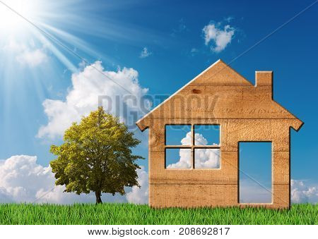Little model of a wooden house on green grass with a tree and a blue sky with clouds and sun rays. Concept of ecological house