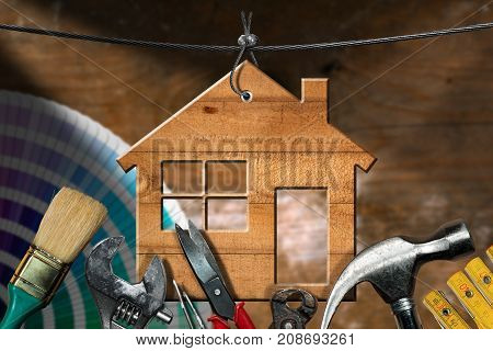 Home improvement concept - Wooden model house hanging on a steel cable with work tools