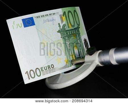 Hundred euro in micrometer on black background