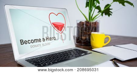 Become a Hero text with heart shape on screen against office desk with laptop and documents
