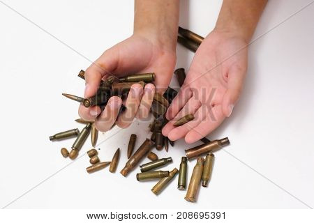 Bullets, cartridges in children's hands In children's pockets on a white background bullets and cartridges of war. Isolated