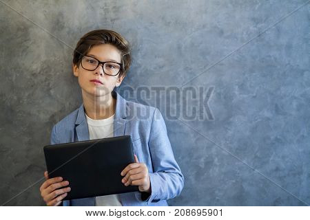 Teen Boy Wearing Glasses Standing By The Wall With Tablet In His Hands