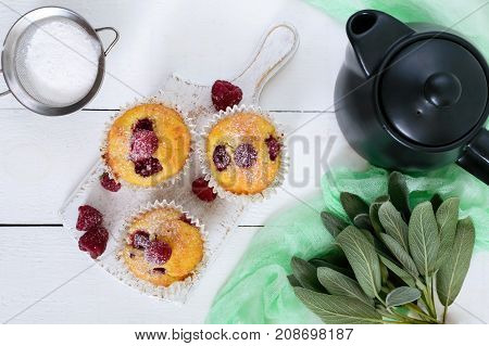 Delicious freshly baked muffins with raspberries decorated with powdered sugar teapot on a white wooden background. Top view.
