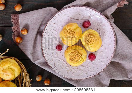 Delicious profiteroles with caramel nut cream on a ceramic plate on a dark wooden background. Top view.