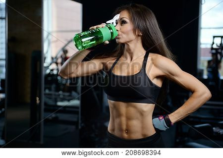 Sexy Athletic Young Girl Takes Sport Nutrition