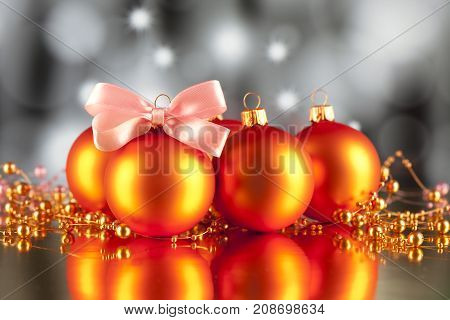 Christmas baubles ornaments and pink bow on abstract background