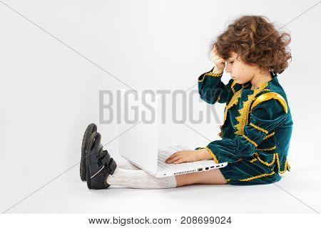 Kid Is Surprising On Dangerous Contents On Internet. Personal Computer And A Boy Dressed As A King