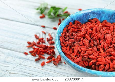 Bowl with red dried goji berries on wooden table