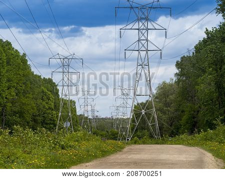 High voltage tower with dramatic clouds and blue sky during sunny day.