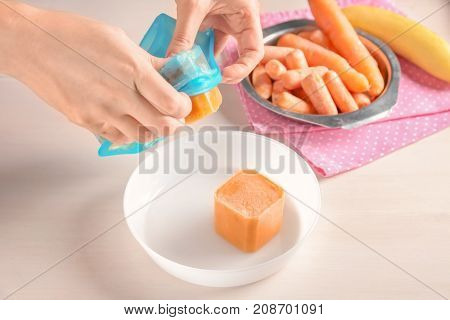 Woman removing frozen vegetable puree from silicone ice tray, closeup