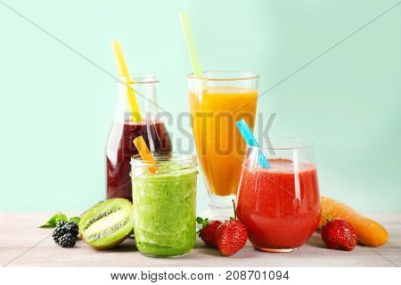 Glassware with delicious smoothies on table against color background