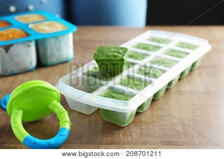 Ice tray with frozen vegetable puree on wooden table