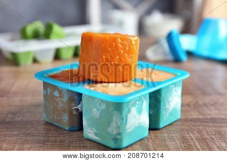 Silicone ice tray with frozen vegetable puree on wooden table