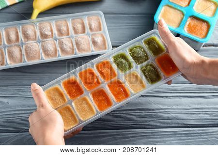 Woman holding ice tray with frozen vegetable puree near table